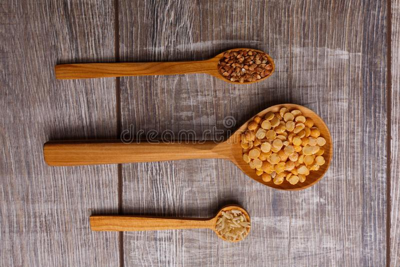 Drei verschiedene hölzerne Löffel mit Getreide liegen horizontal und entsprechen rechts lizenzfreie stockfotografie