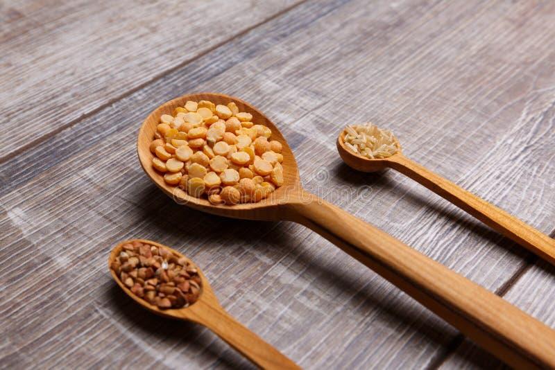 Drei verschiedene hölzerne Löffel mit Nahaufnahme der Getreide auf dem Tisch stockfotografie
