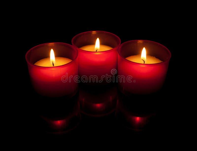 Drei votive Kerzen, rote Halterungen mit Reflexionen lizenzfreie stockfotografie
