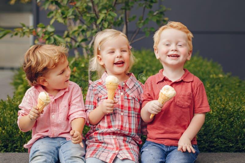 Drei weiße kaukasische nette entzückende lustige Kinderkleinkinder, die Eiscreme sitzen zusammen, teilend stockfotos