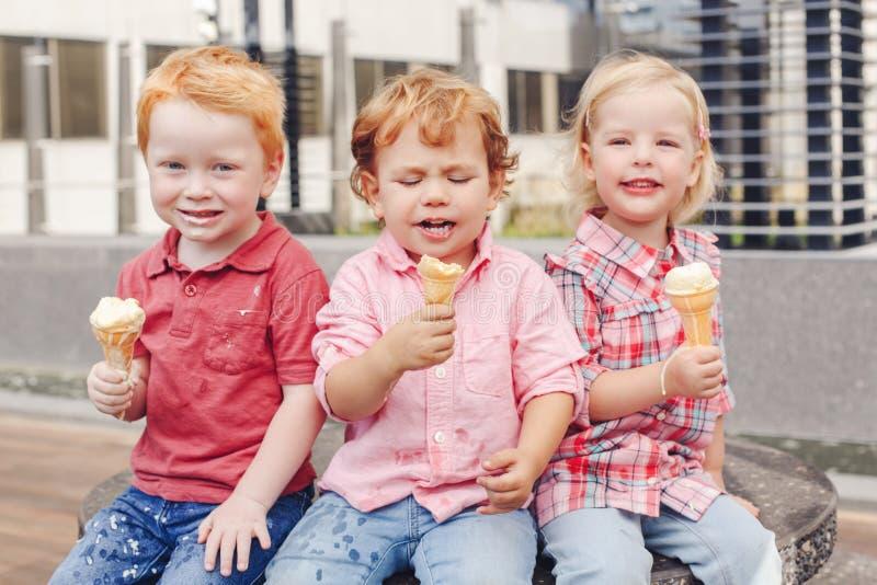 Drei weiße kaukasische nette entzückende lustige Kinderkleinkinder, die Eiscreme sitzen zusammen, teilend lizenzfreie stockfotografie