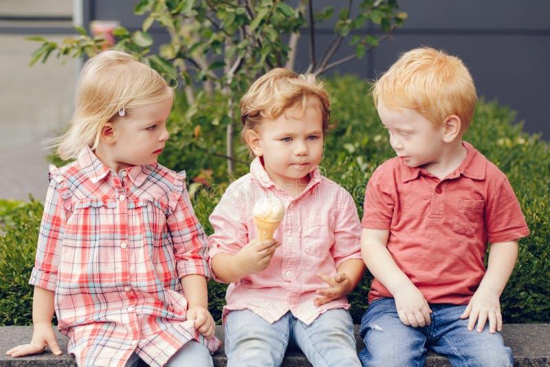 Drei weiße kaukasische nette entzückende lustige Kinderkleinkinder, die Eiscremesitzen Lebensmittel zusammen, teilend lizenzfreie stockbilder