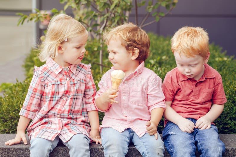 Drei weiße kaukasische nette entzückende lustige Kinderkleinkinder, die Eiscremesitzen Lebensmittel zusammen, teilend lizenzfreie stockfotografie