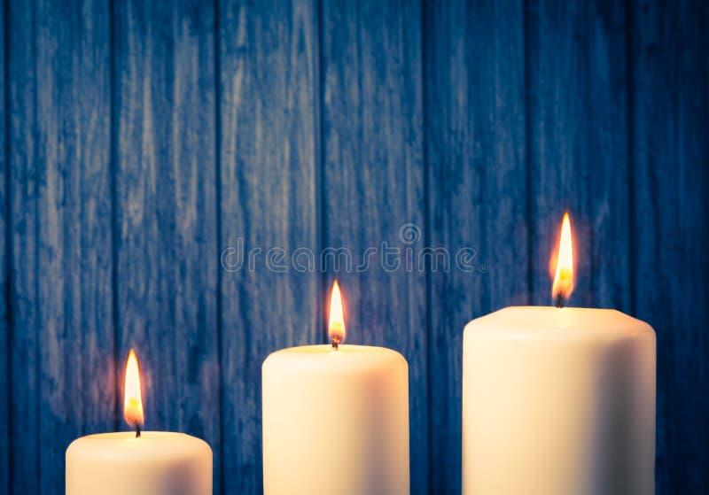 Drei weiße Kerzen auf warmer Atmosphäre lizenzfreies stockbild