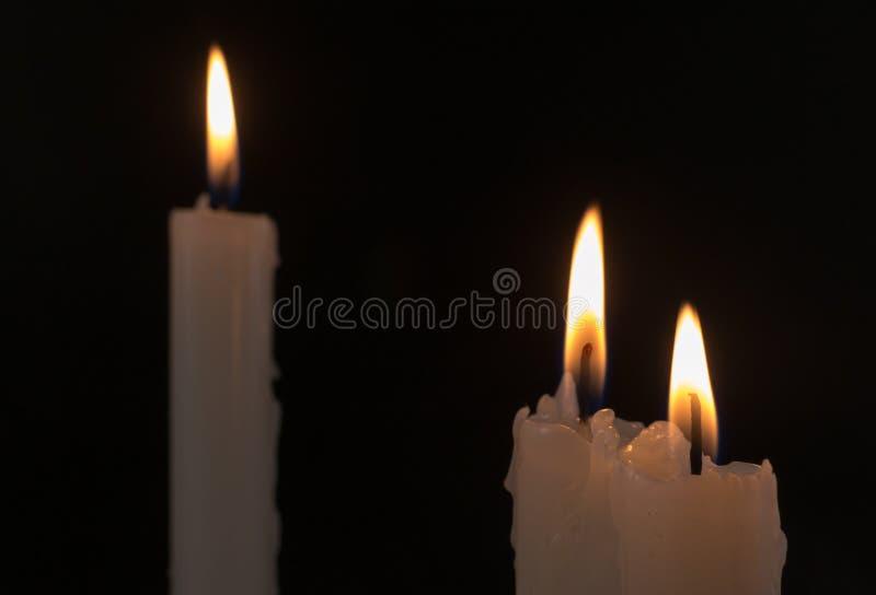 Drei weiße Kerzen in der Nacht brennend stockfotografie