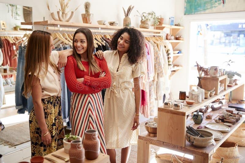 Drei weibliche Fachverkäufer, die in der Kleidung und im Geschenkladen arbeiten stockfoto