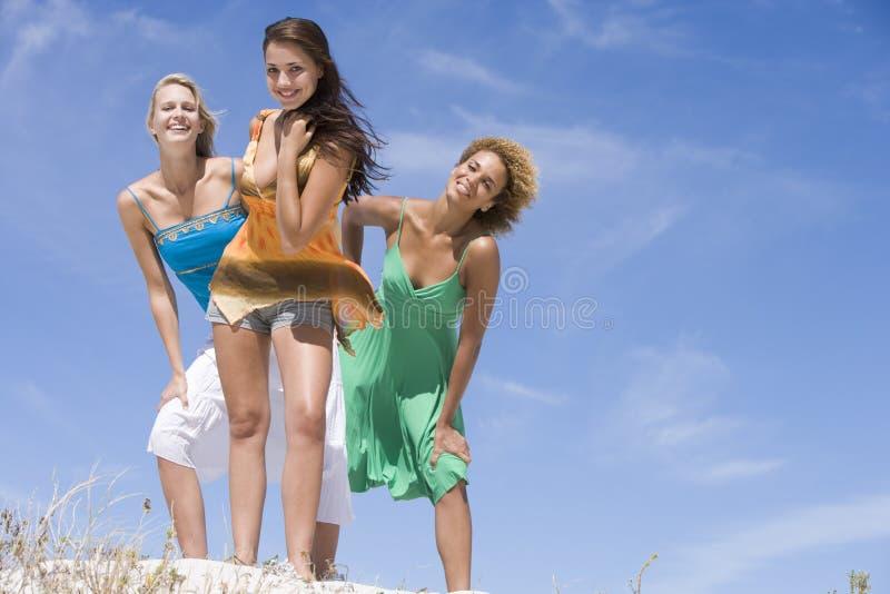 Drei weibliche Freunde, die am Strand sich entspannen stockfotografie