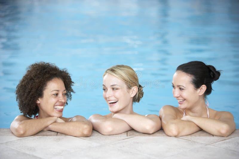 Drei weibliche Freunde im Swimmingpool stockbilder