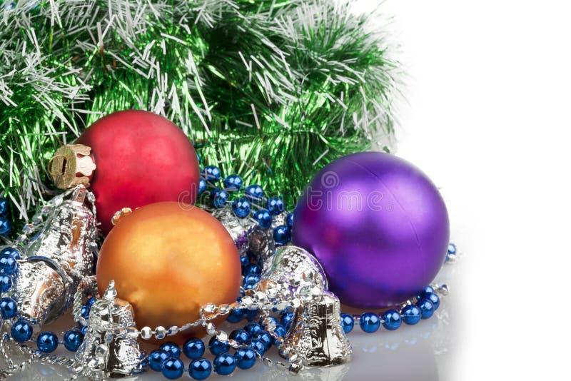 Drei Weihnachtsbälle mit blauen Perlen, grüner Girlande und Silber stockfoto