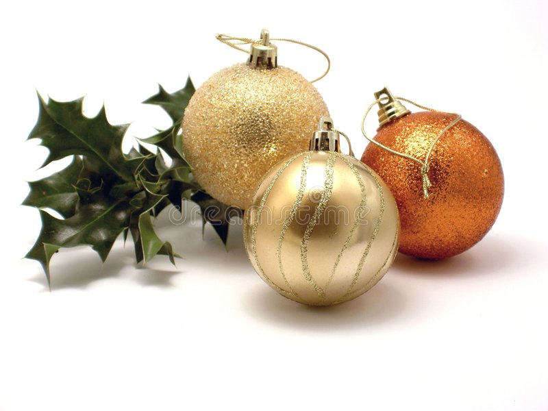 Drei Weihnachtsdekorationen und -stechpalme stockfotos
