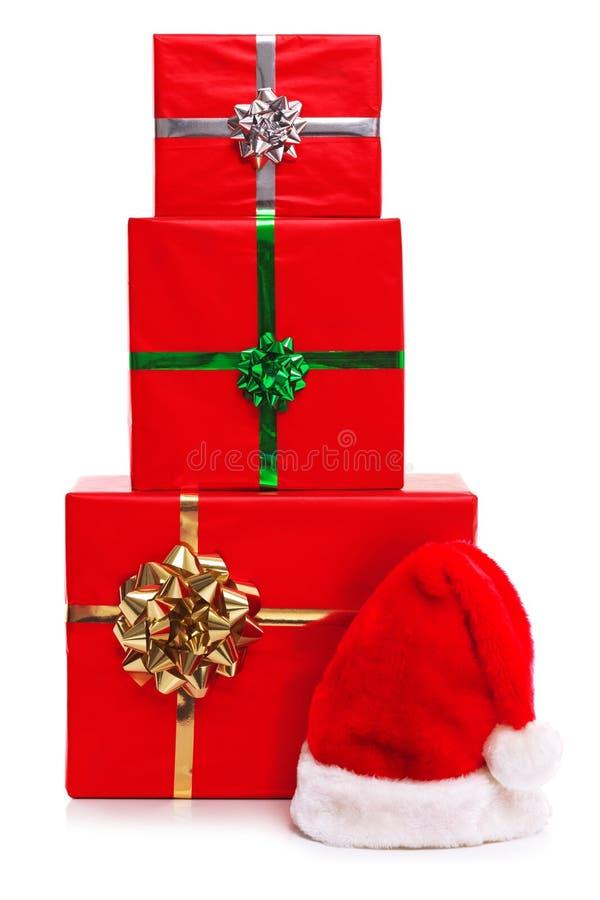 Drei Weihnachtsgeschenke und Weihnachtsmann-Hut. stockfoto