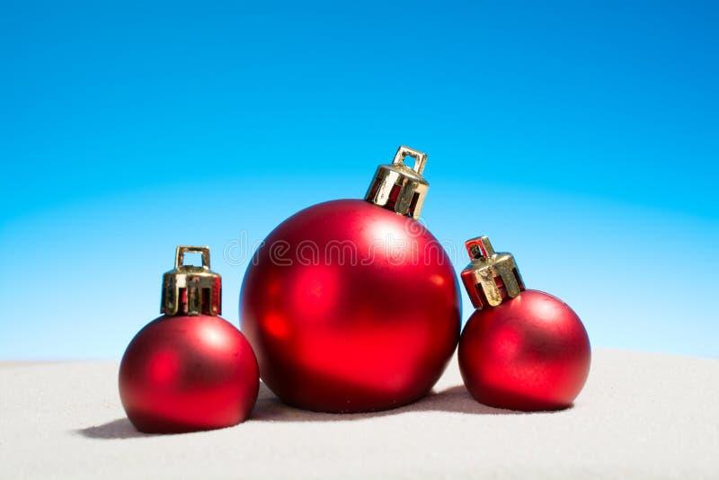 Drei Weihnachtsglaskugeln auf dem Strand lizenzfreies stockfoto