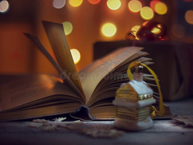 Drei Weihnachtskugeln getrennt auf Weiß Geöffnetes Buch von Märchen und von Weihnachtsdekorationen auf einem Holztisch stockfotos
