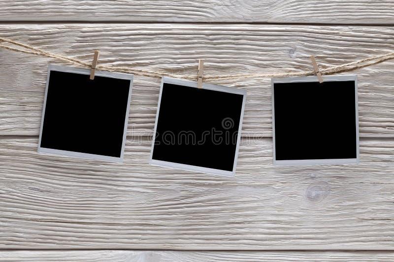 Drei Weinlesefotorahmen mit leerem Raum auf Seil und hölzernem Hintergrund lizenzfreie stockfotografie