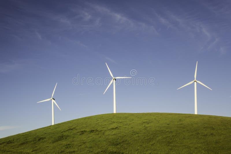 Drei Windkraftanlagen auf einem Hügel lizenzfreie stockfotografie