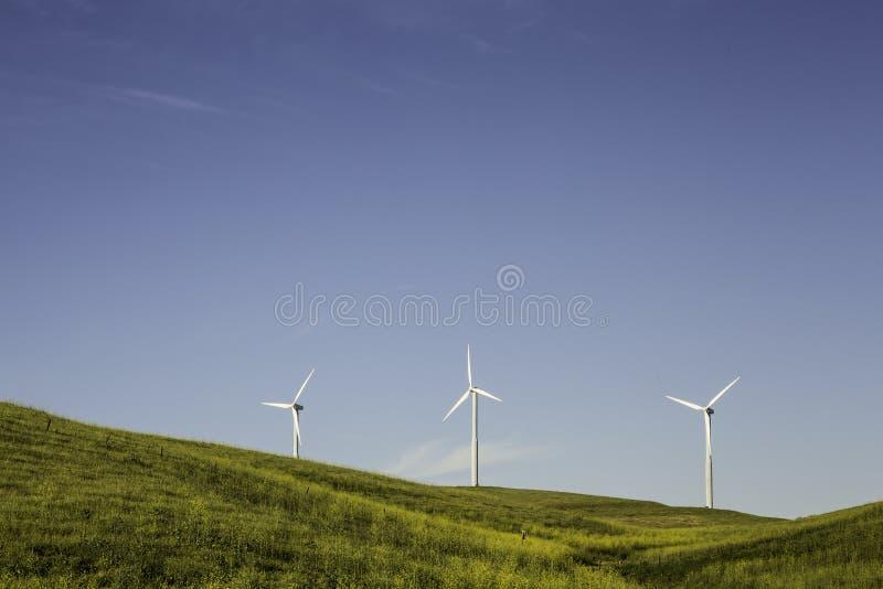 Drei Windkraftanlagen in einem Tal stockfotografie
