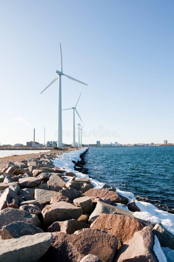 Drei Windmühlen nähern sich gefrorenem See stockbild