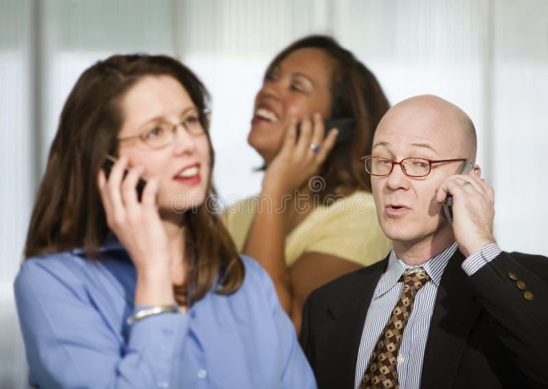 Drei Wirtschaftler auf Handys stockfotografie