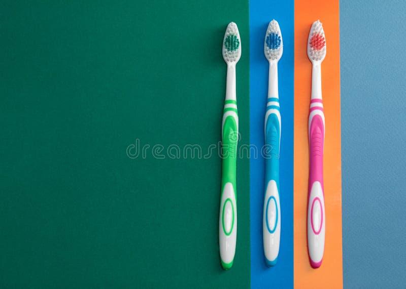 Drei Zahnbürsten auf farbigem Papier stockbilder