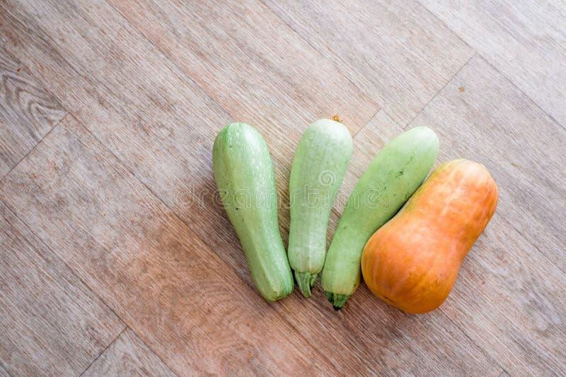 Drei Zucchini und ein Kürbis auf hölzernem Beschaffenheitshintergrund lizenzfreie stockfotografie