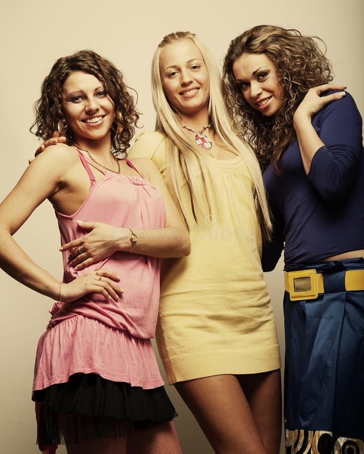 Drei zusammen lächelnde Freundinnen lizenzfreies stockbild