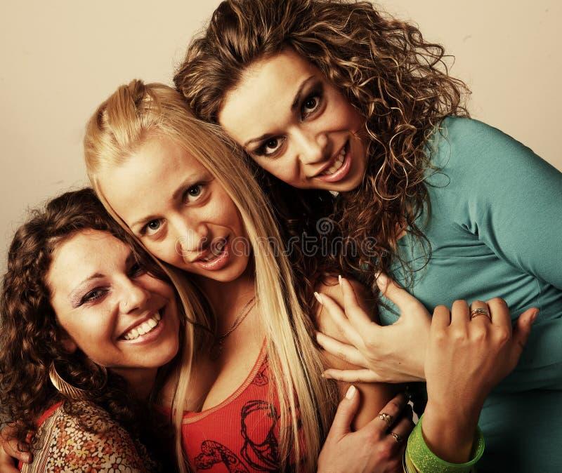 Drei zusammen lächelnde Freundinnen stockfotos