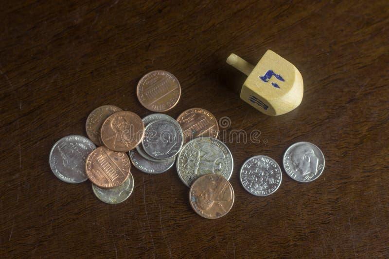 Dreidel de madeira entre moedas americanas dispersadas foto de stock royalty free