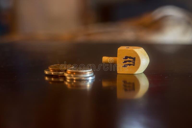 Dreidel de madera al lado de la pila de monedas fotos de archivo