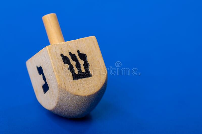 Dreidel or dreydl on blue background stock image