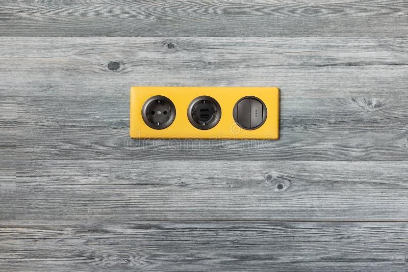 Dreifacher heller gelber Rahmen mit Netzdose, USB-Porten und hellem Schlüsselschalter auf grauer hölzerner Wand lizenzfreie stockfotografie