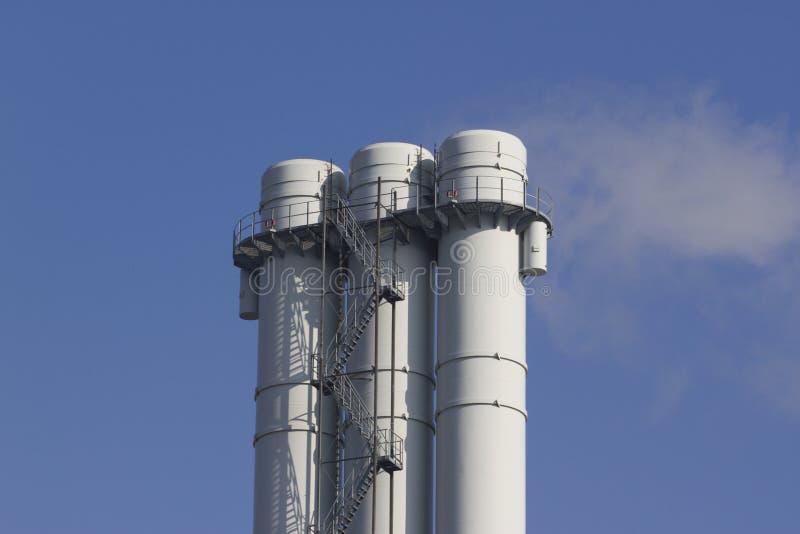 Dreifaches Rohr strahlt Rauch gegen den blauen Himmel aus stockbild