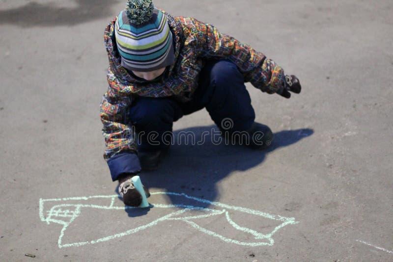 Dreijähriger Junge in farbiger Oberbekleidung und in Hut zeichnet Kreide auf dem Asphalt im Vorfrühling stockfotografie