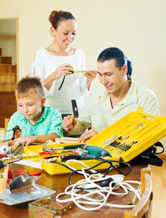 Dreiköpfige Familie, die etwas mit den Arbeitsgeräten tut stockbild