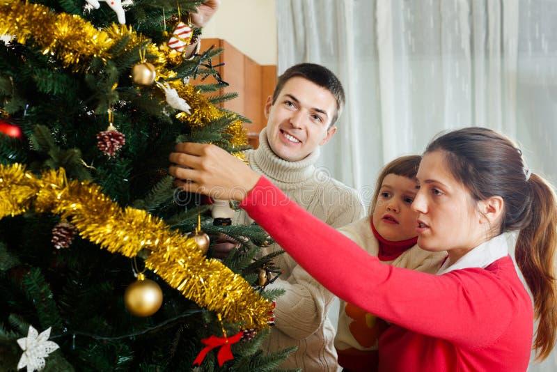 Dreiköpfige Familie, die für Weihnachten sich vorbereitet lizenzfreies stockbild