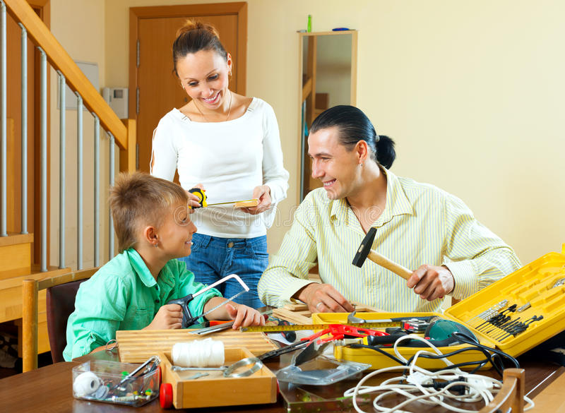 Dreiköpfige Familie mit dem Teenager, der etwas mit dem worki macht lizenzfreie stockbilder