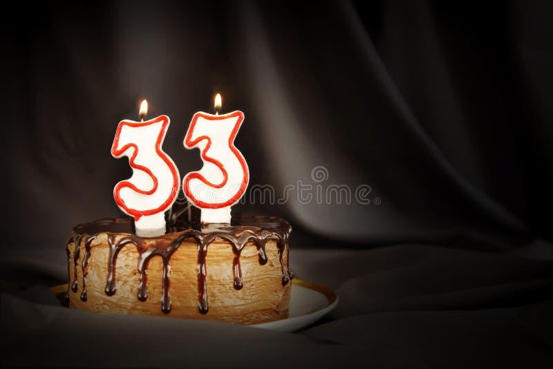 Dreiunddreißig Jahre Jahrestag Geburtstagsschokoladenkuchen mit weißen brennenden Kerzen in Form von Nr. dreiunddreißig stockfotografie