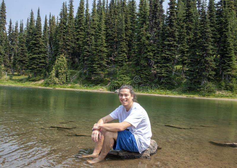 Dreiundzwanzig Jährige Amerasian-Mann, der einen Bruch von einer Wanderung im Berg Rainier National Park, Washington genießt lizenzfreie stockfotos