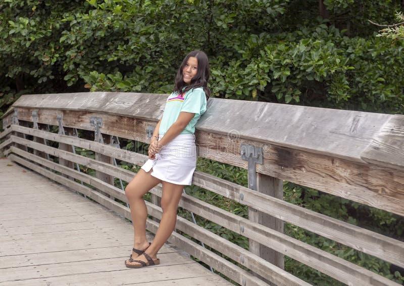 Dreizehn jähriges Amerasian Mädchen, das auf einer Holzbrücke in Washington Park Arboretum, Seattle, Washington aufwirft stockbild
