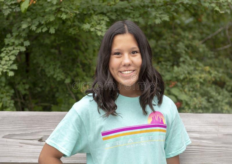 Dreizehn jähriges Amerasian Mädchen, das auf Holzbrücke in Washington Park Arboretum, Seattle, Washington aufwirft lizenzfreies stockfoto