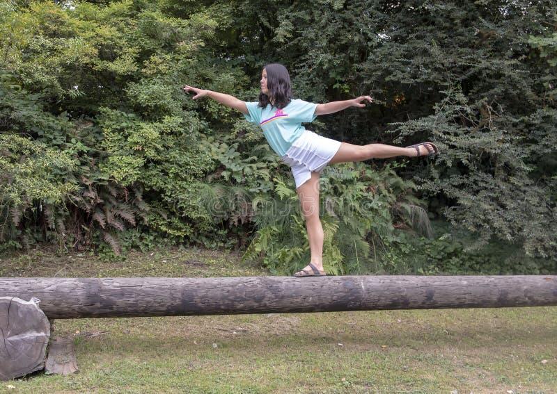 Dreizehn jähriges Amerasian Mädchen in einer Tanzhaltung auf einem Klotz, Washington Park Arboretum, Seattle, Washington lizenzfreie stockfotos