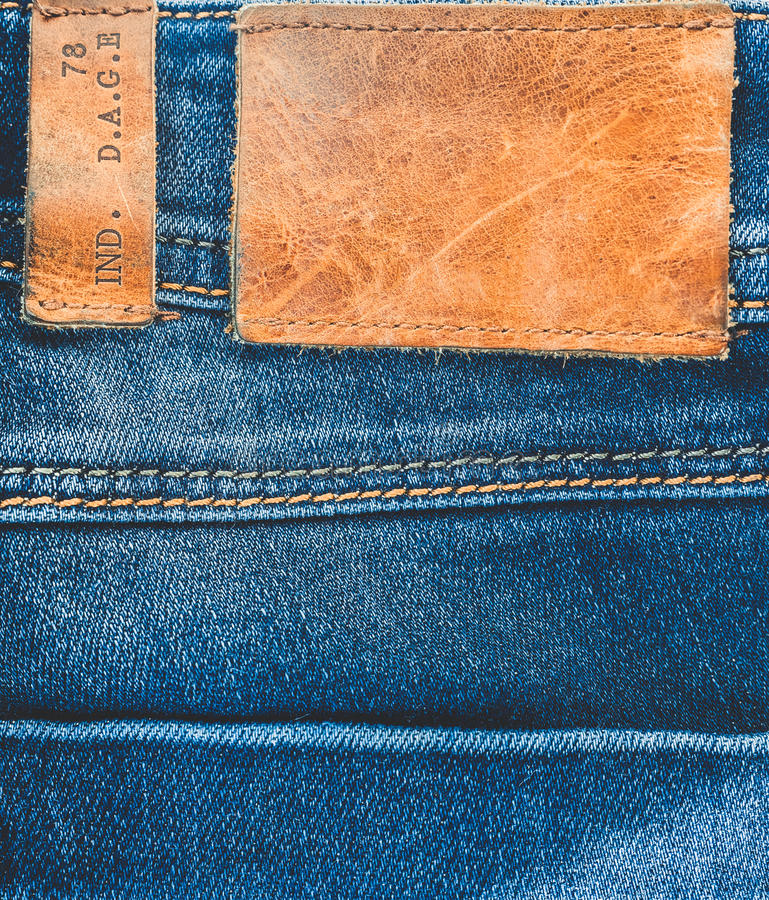 Drelichowy tło Niebiescy dżinsy z brown rzemienną etykietką opróżniają przestrzeń obrazy royalty free