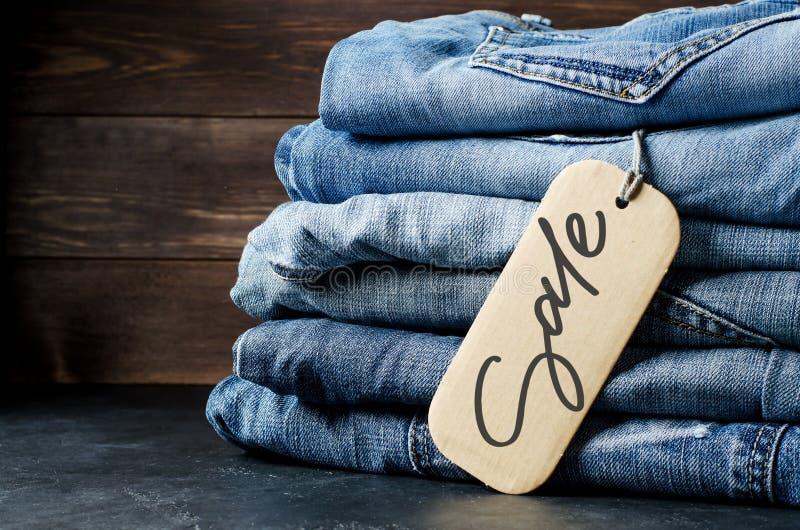 drelichy. Mnóstwo niebieskich dżinsów na drewnianym tle. Sprzedaż — napis odrÄ™czny na papierowej etykiecie zdjęcia royalty free