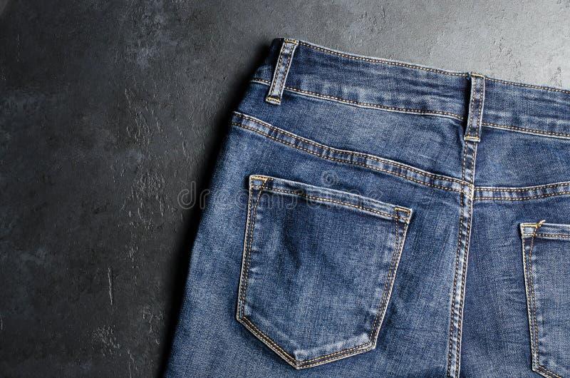 drelichy. Niebieskie dżinsy na czarnym tle. z bliska obraz royalty free