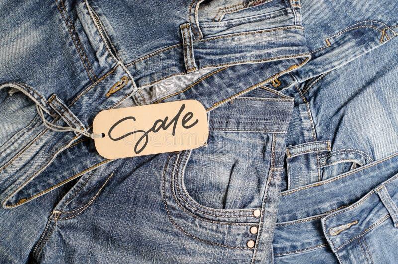 drelichy. Niebieskie dżinsy na ladzie sklepowym. Sprzedaż — napis odrÄ™czny na papierowej etykiecie zdjęcia royalty free