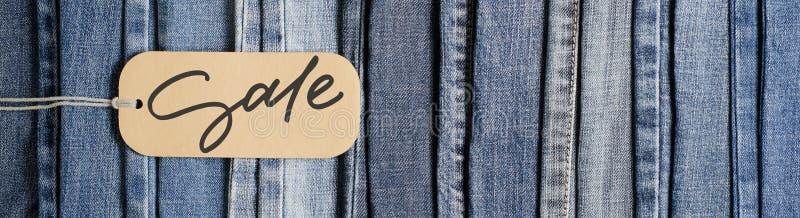 drelichy. t?o drelich?w konsystencja ubraniowa d?insy blue. Sprzedaż — napis odrÄ™czny na papierowej etykiecie zdjęcia royalty free