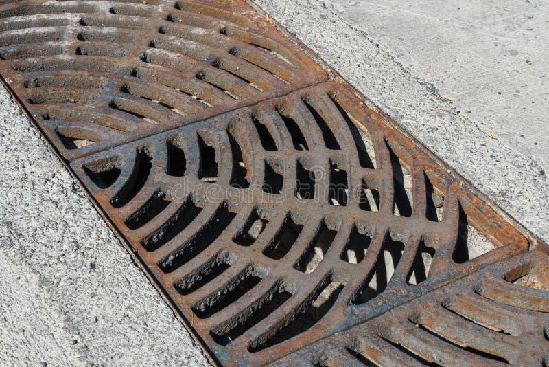 Dren de la rejilla del metal alrededor con el camino áspero del beton foto de archivo libre de regalías