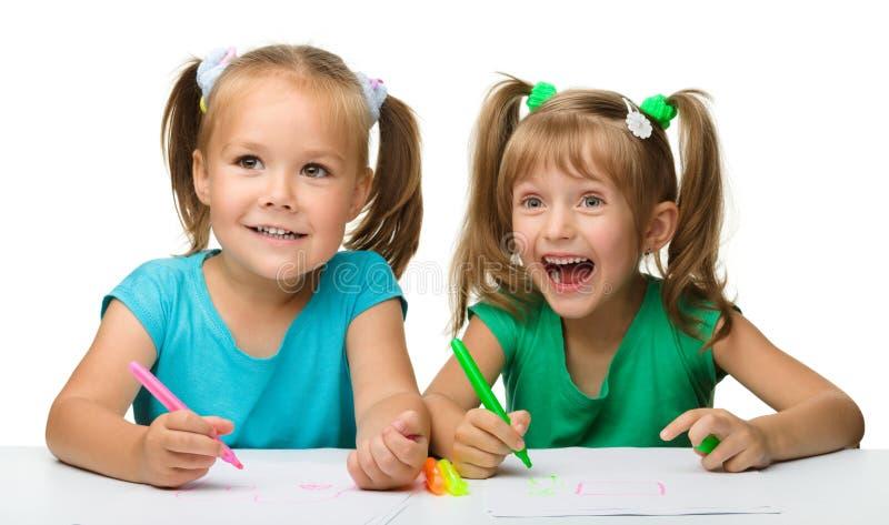 Drenaje de dos niñas con las etiquetas de plástico imágenes de archivo libres de regalías