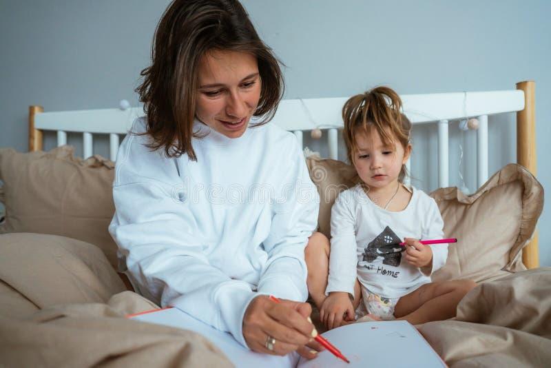 Drenaje de la mamá y de la hija en cama imágenes de archivo libres de regalías