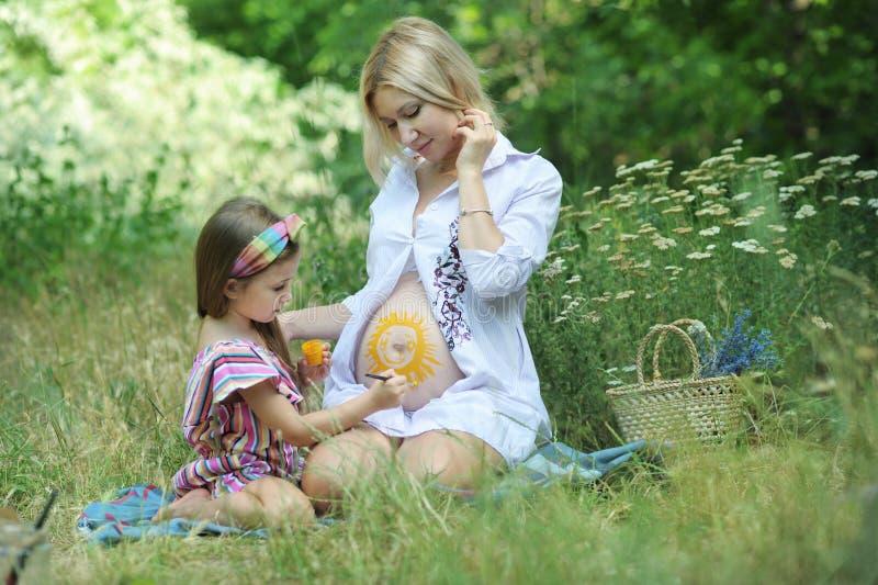 Drenaje de la niña un sol en su estómago embarazada de la madre imagenes de archivo