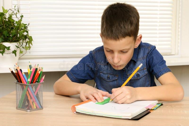 Drenaje del muchacho en cuaderno Niño que se sienta en el hogar del escritorio y que hace su preparación Escuela, niños, concepto foto de archivo libre de regalías